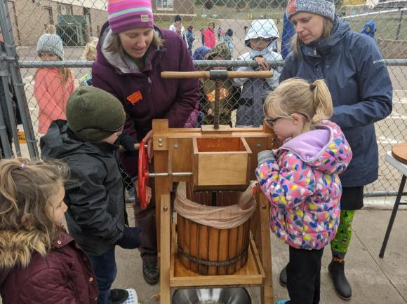 Community Partner, Kathleen Harter, assists students from Mrs. Nolan�s Kindergarten class during apple cider-making using a hand-cranked apple cider press.